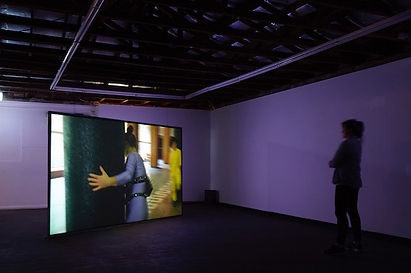 A gallery with a video installation. A single screen stands upright from the ground. The image depicts a performer wearing a purple outfit and a guitar strapped to their body. A solo viewer stands, silhouoetted, watching the video. The room is illuminated purple.