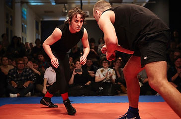 A man and woman stand, crouched, about to freestyle wrestle. A crowd surrounds them. They are in the middle of a gallery space.