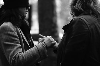 A woman with her eyes covered holds the hand of another woman. Both if them wear large jackets.