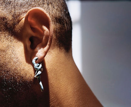 An image of a person's ear in close detail. Their head is angled slightly downward. Their hair is short cropped and they have close cropped stubble which catches the light. They wear an earring which curls, worm like, out of the pierced hole.