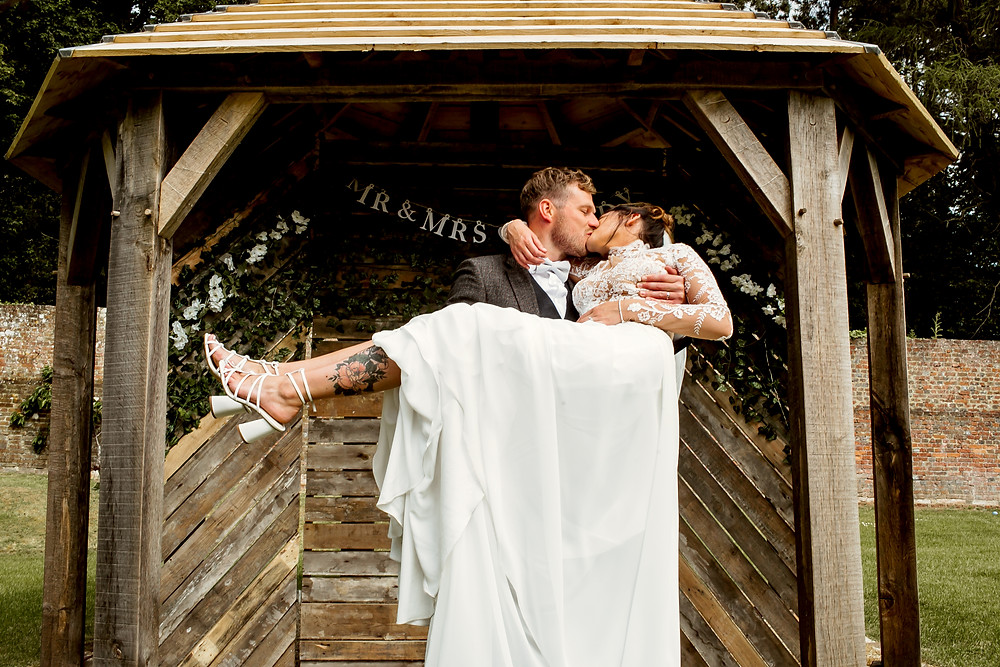 Tattooed wedding couple kissing under an arch