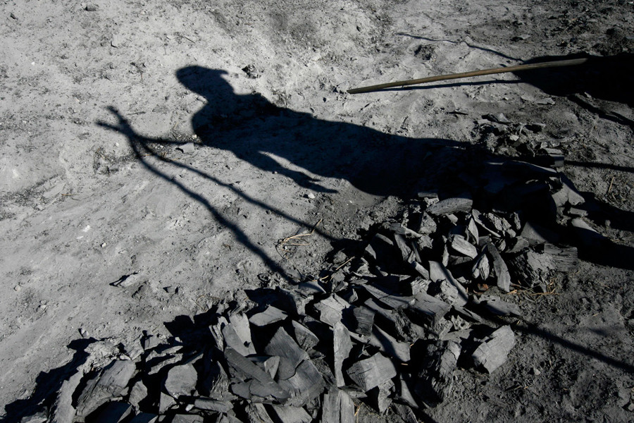 The shadow of a coal worker is cast on the floor next to ash and pieces of coal in the Cienega de Zapata, Cuba February 5, 2009. Photo/Enrique De La Osa