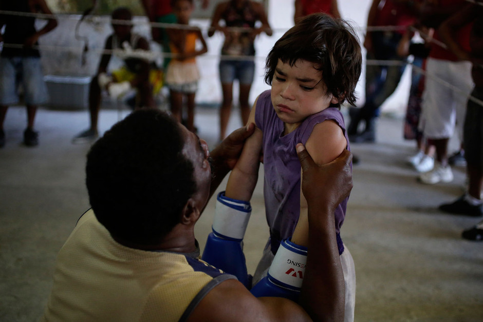 A boxer is helped from a teacher after receives a punch from an opponent during a exhibition tournament in Havana, Cuba, March 22, 2014.  Photo/Enrique de la Osa