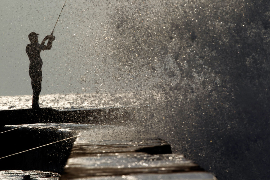 "A man fish as a wave breaks on Havana's seafront boulevard ""El Malecon"" October 1, 2010. Photo/Enrique De La Osa"