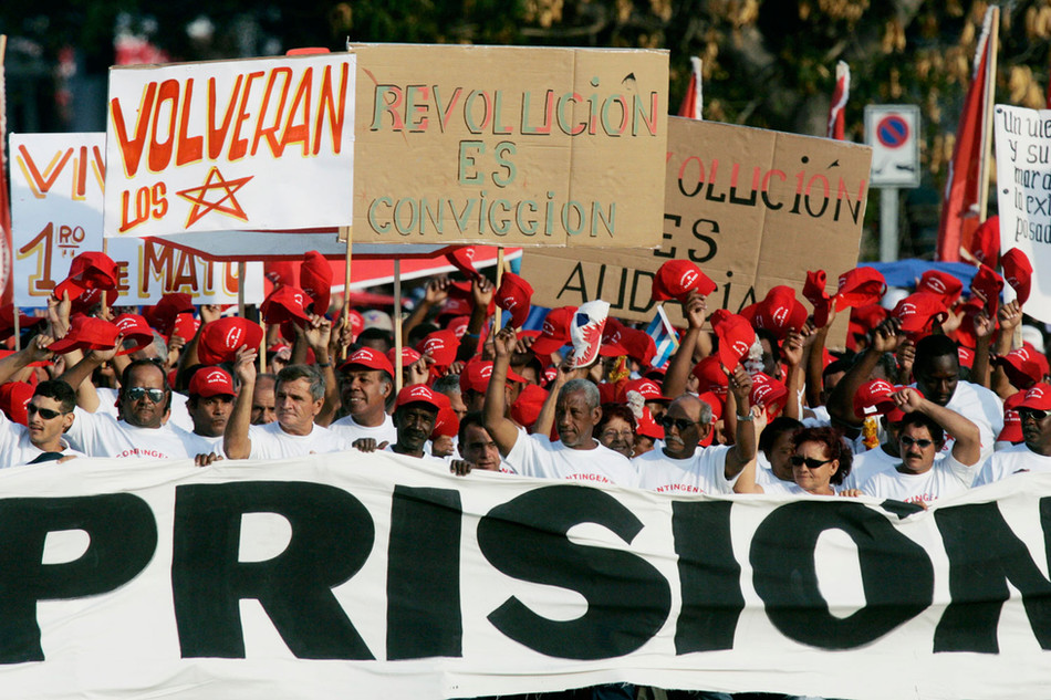 """Cubans hold a banner that reads """"Prison"""" in reference to former CIA operative Luis Posada Carriles accused of bombing a Cuban airliner 30 years ago and recently freed on bail in the U.S., during a May Day parade in Revolution Square in Havana, May 1, 2007. Photo/Enrique de la Osa"""
