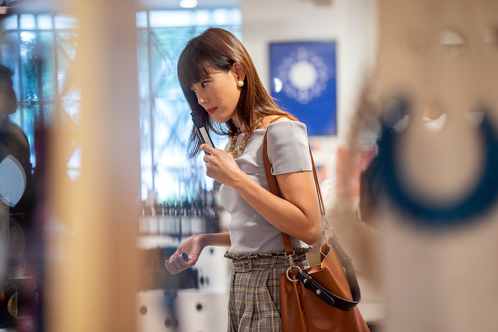 A shopper walks around a retail store with a credit card in hand.