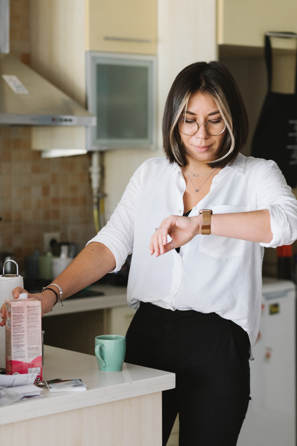 A woman checks her watch while standing in a kitchen.