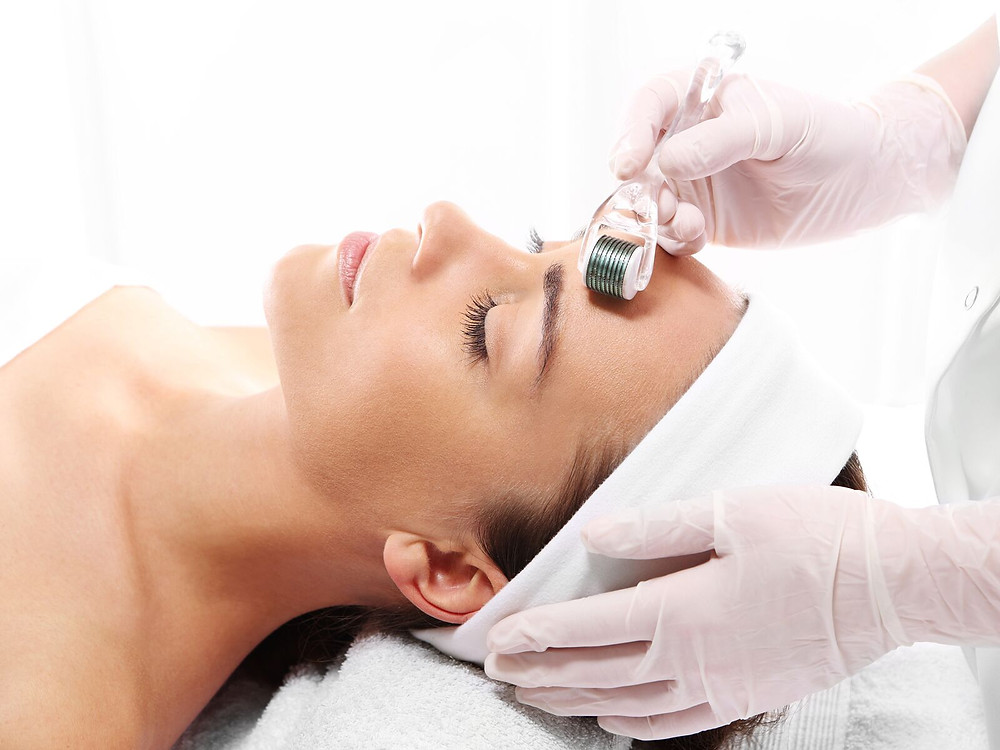 A person relaxes on a bed while undergoing a micro-needling session using a derma roller device..