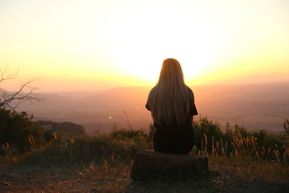 A person sits on a tree stump and watches a sunset to recover from narcissistic abuse.