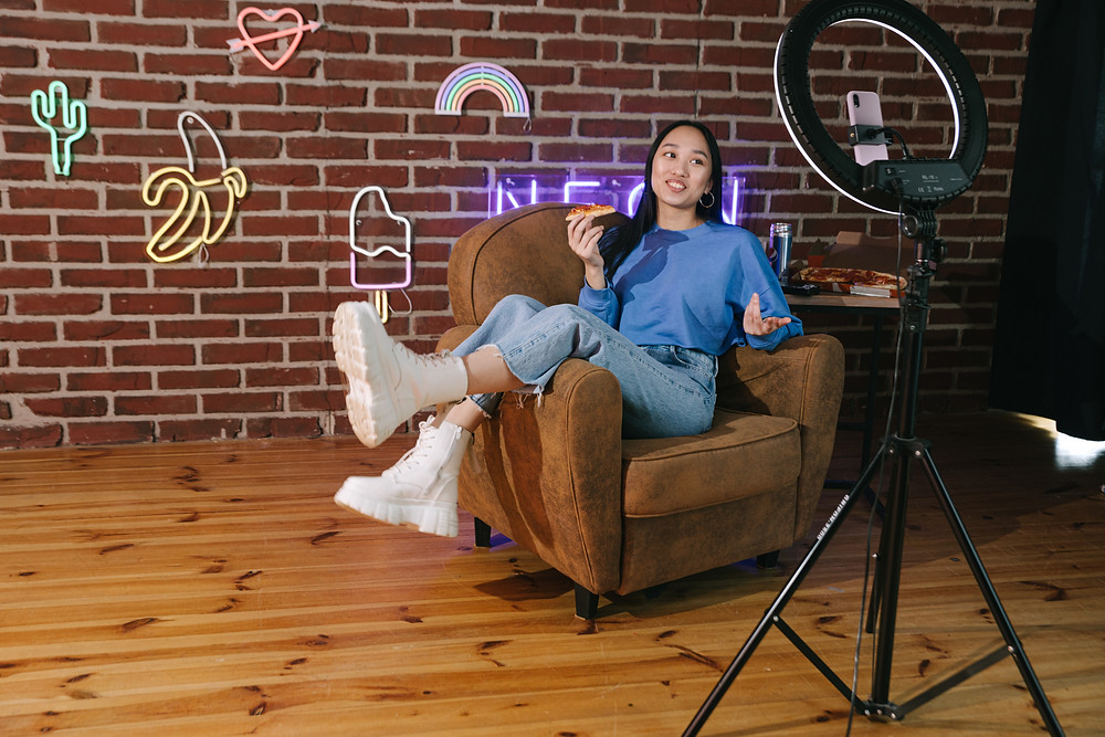 A content creator lounges in an arm chair while holding a slice of pizza and poses against a brick wall back drop, illuminated by a ring light stand.