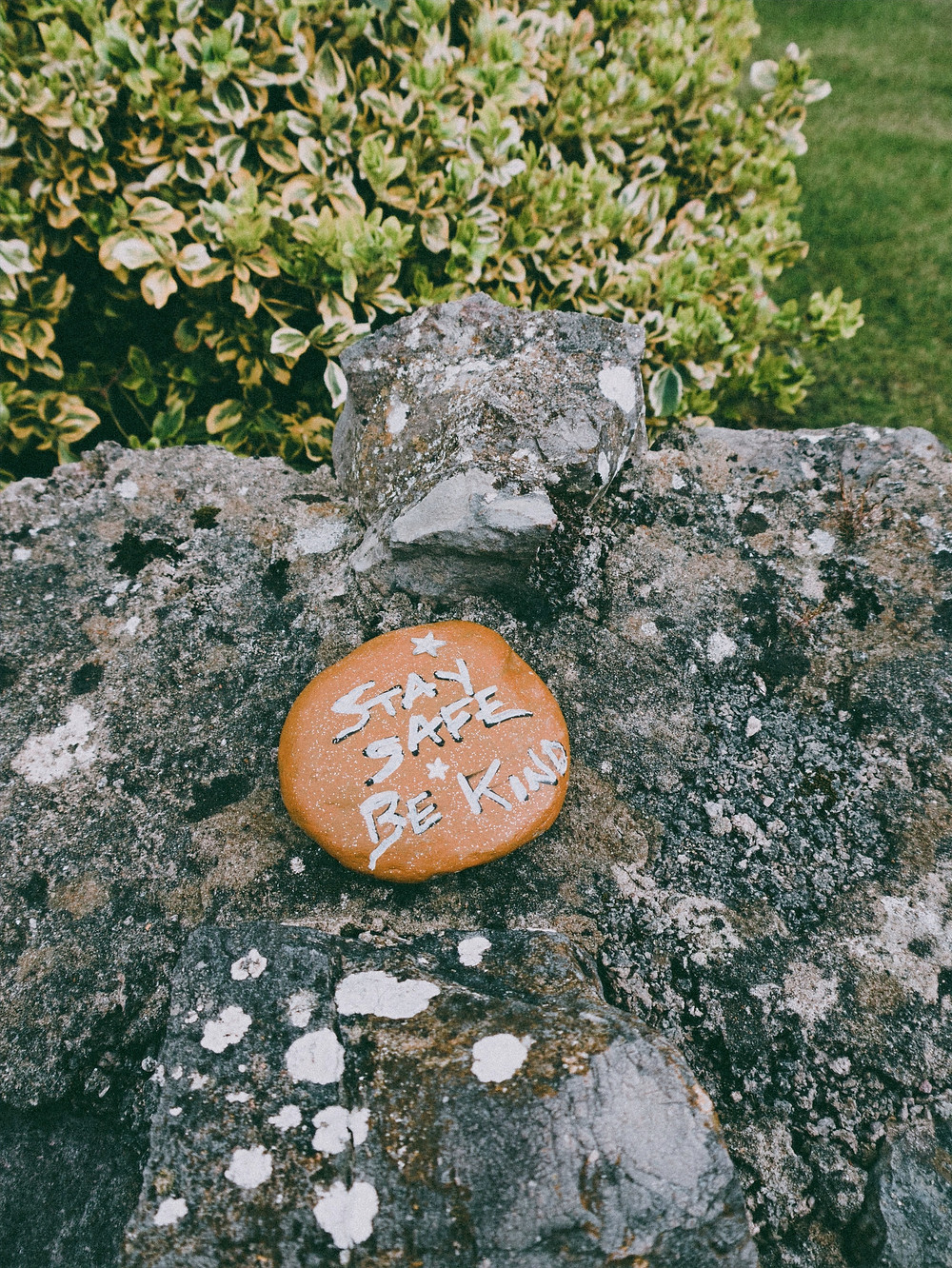 "A photograph of an orange stone, resting on a larger grey stone and bush, painted with the words, ""stay safe + be kind"""