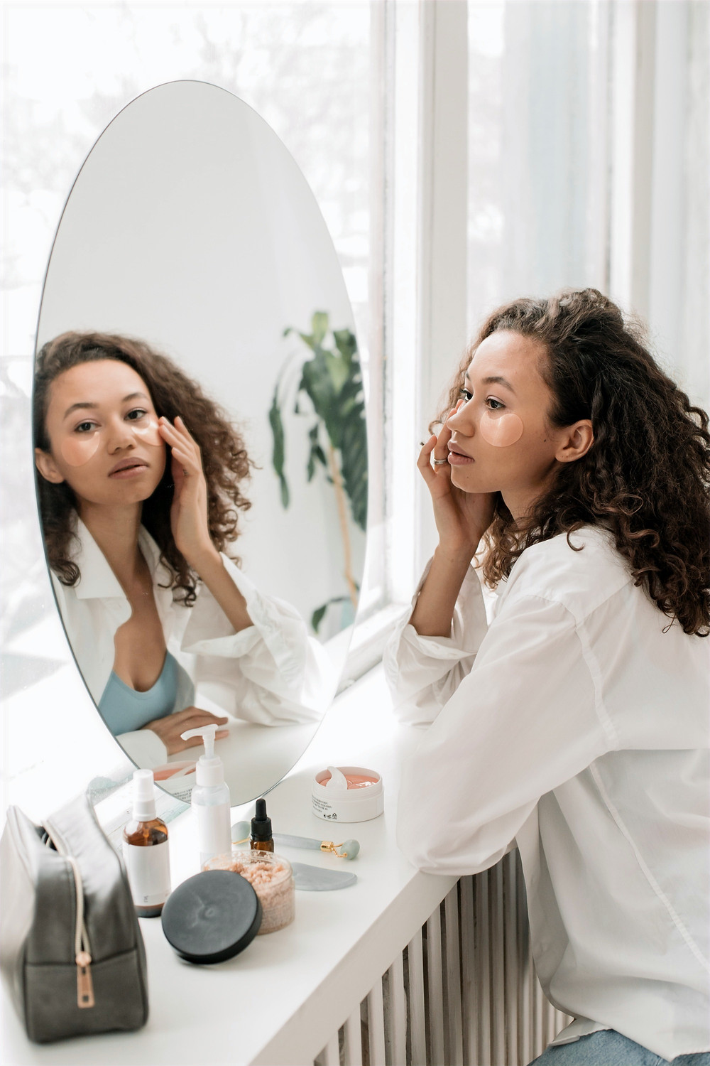 A woman looks in the mirror in a white minimalist room while attending to her skin her the reflection.