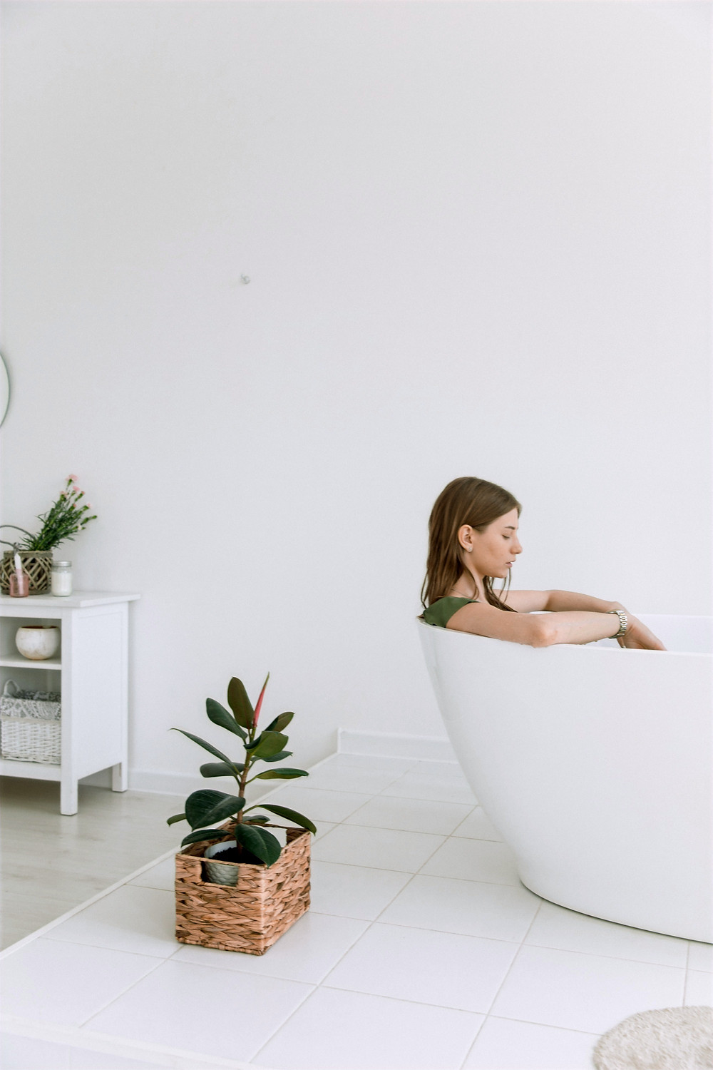 A photograph of a person sitting in a minimalist white bathtub, practicing a wellness ritual for self-compassion..