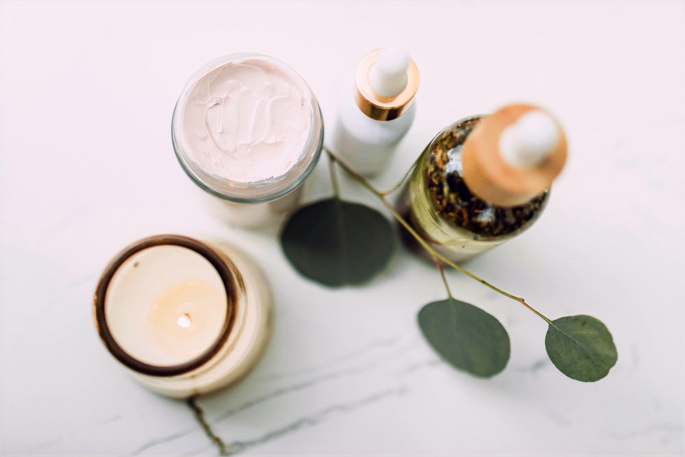 A candle, skin cream, and skin serums are pictured with a minimalist green plant on a white background.