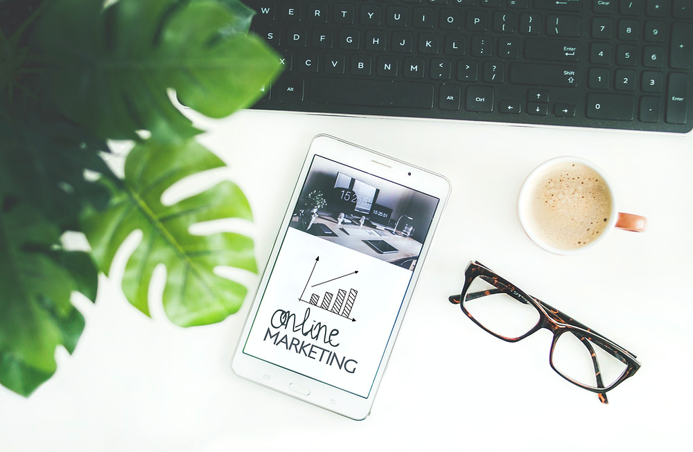 A phone displaying an online marketing image, pair of glasses, and cup of coffee are on a table.