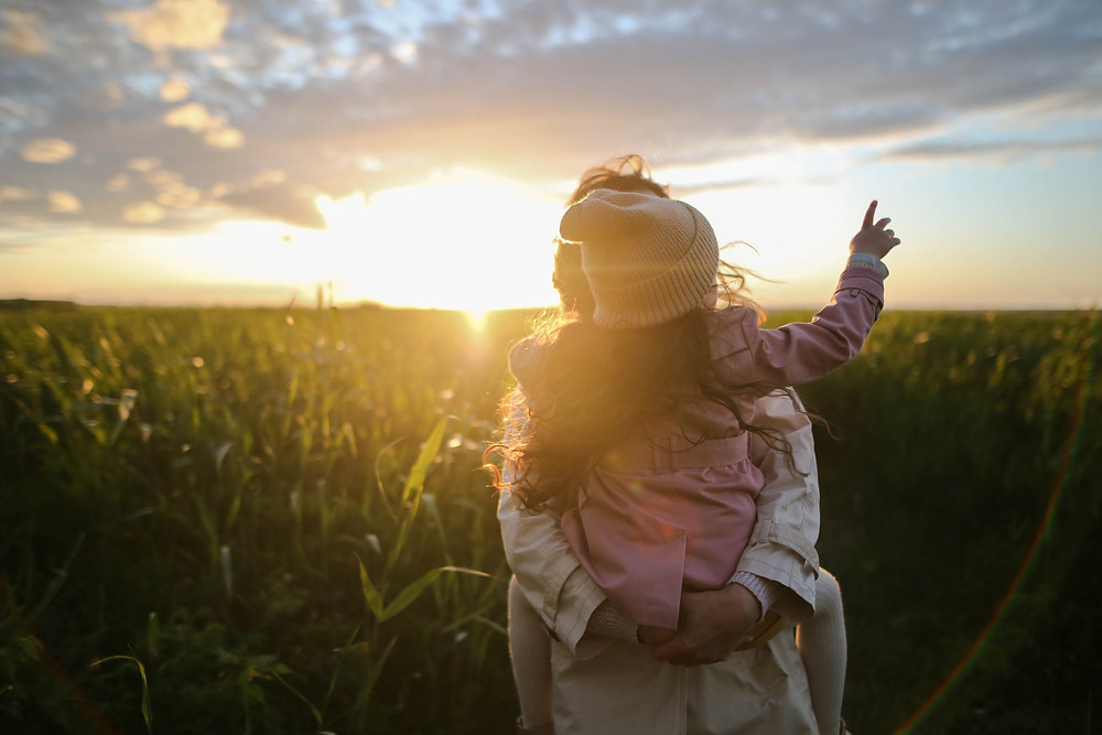 A parent carries a child wearing a beanie while walking through a field at sunset.