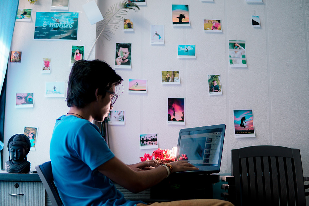 A person navigates an online Fandom community while sitting at a laptop in a room filled with various photographs pinned to a white wall.