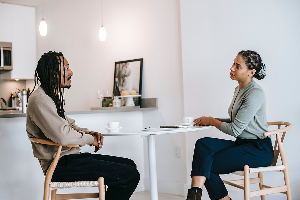 Two people address a lack of empathy by having a conversation over a cup of tea.