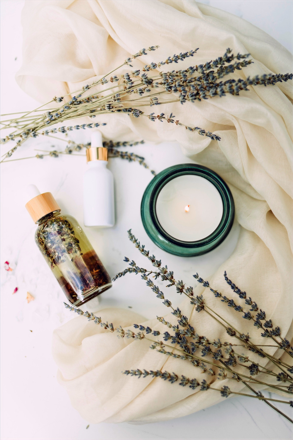 Skin cream, skin serum, a candle, and green plants lay on top of cream-colored sheets against a white background.