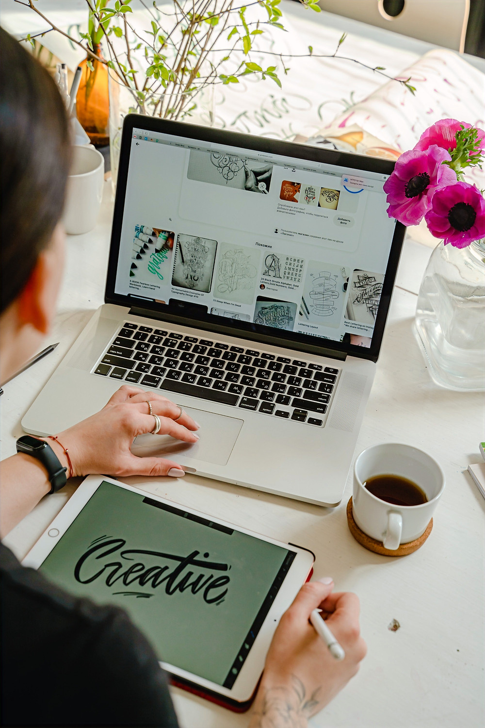 A SEO expert uses a laptop and tablet while creating SEO optimized content.