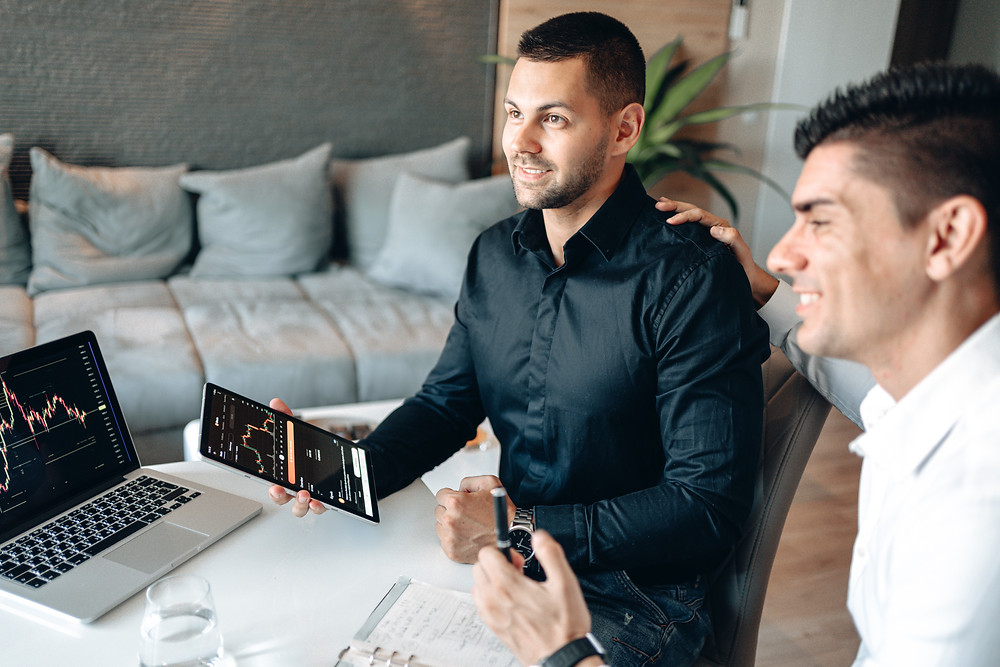 Two digital marketers sit at a table and view the results of a multichannel digital marketing strategy.