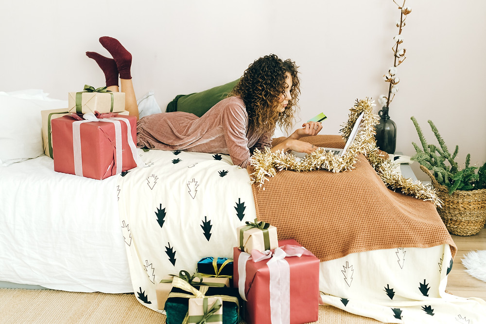 A potential engages in online shopping while laying on a bed surrounded by gifts.