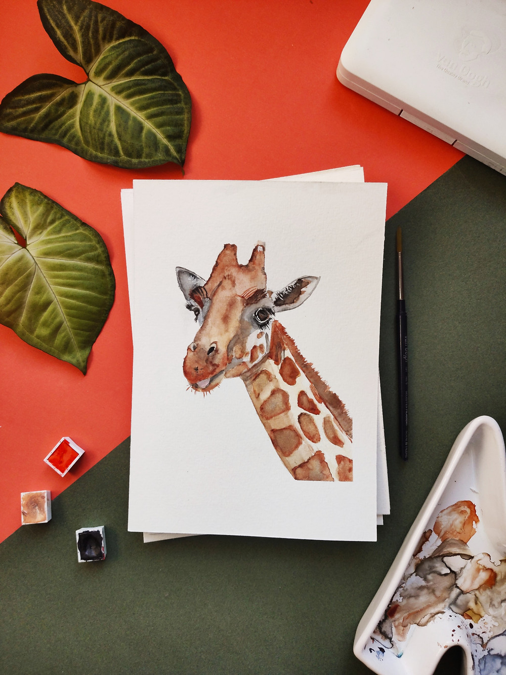 A newly made water color portrait of a giraffe is shown on a table with paint and green leaves.