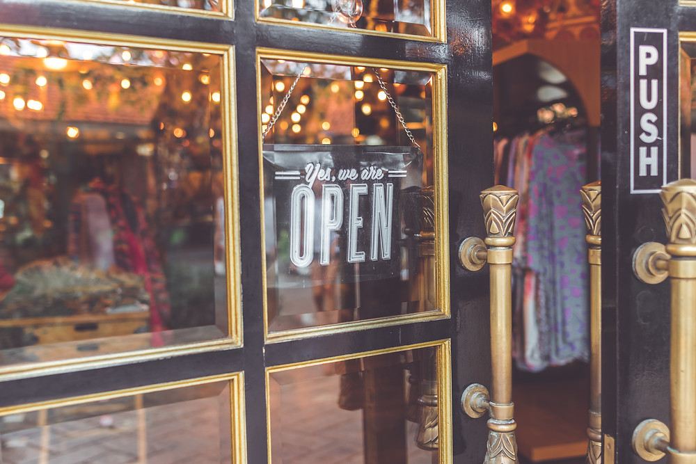 """A sign that says """"Yes, we are open,"""" is shown in the window of a local shop."""