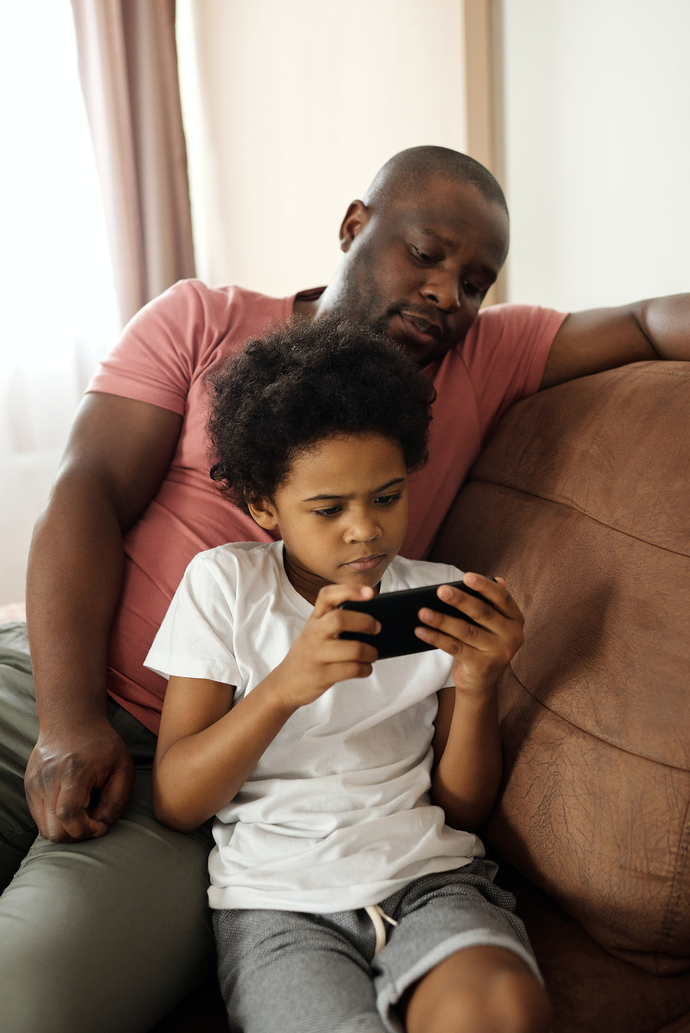 A parent watches a child play a handheld video game while they both sit on a coach.