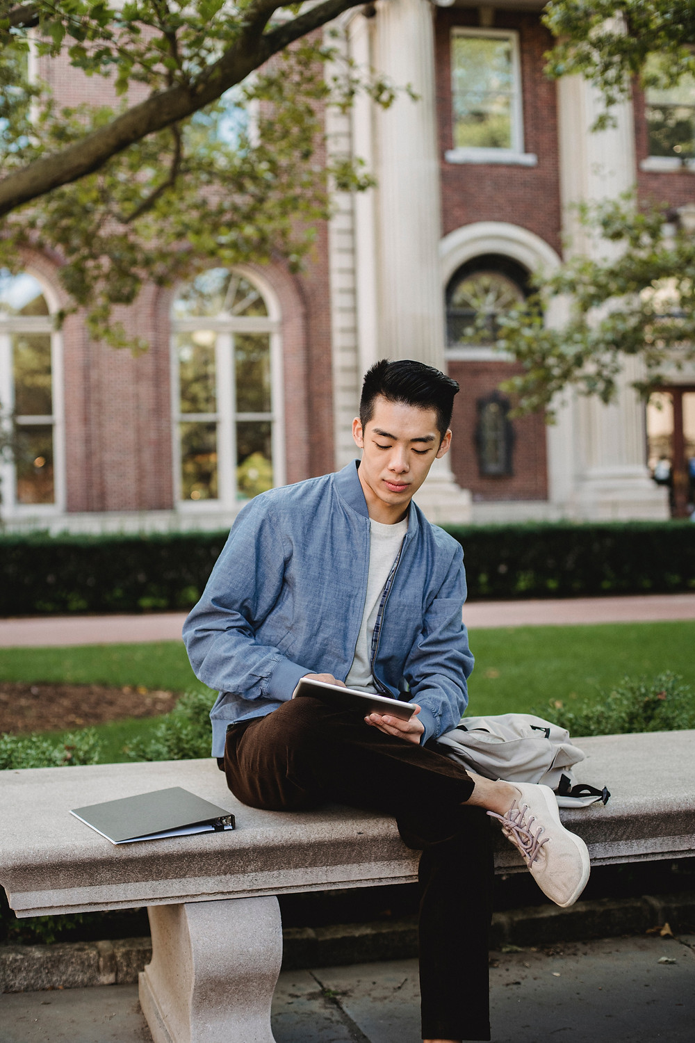 A person reads professional thought leadership on a tablet while sitting outdoors.