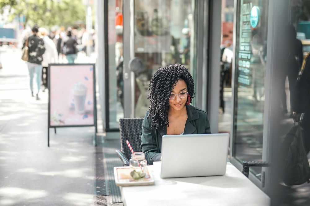 A person sits at an outdoor table while writing on a laptop for a side hustle.