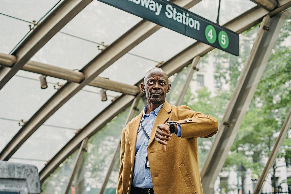 A man checks his watch at a subway station.