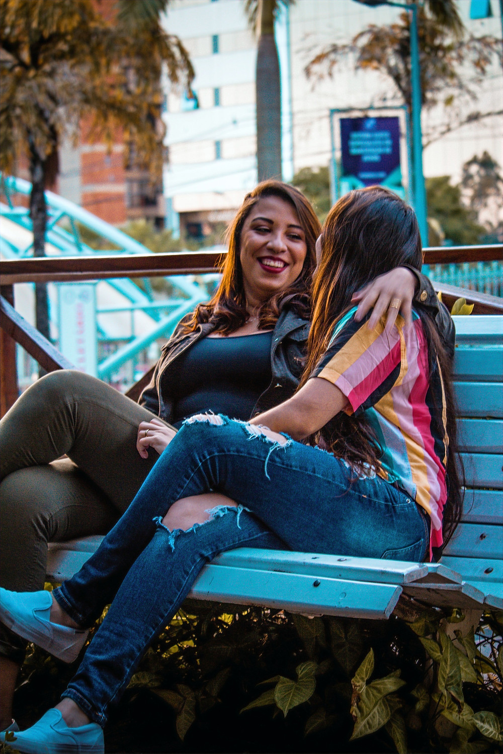 Two people sit on a bench and smile while they empathize with each others' experiences.