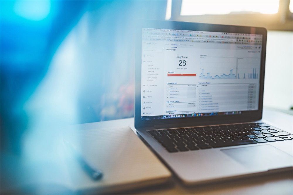 A laptop computer is open to a SEO software that displays keyword research.