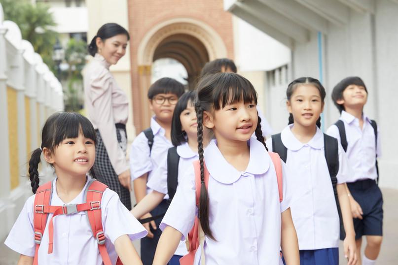 Vietnamese Elementary school children walking to class with her teacher