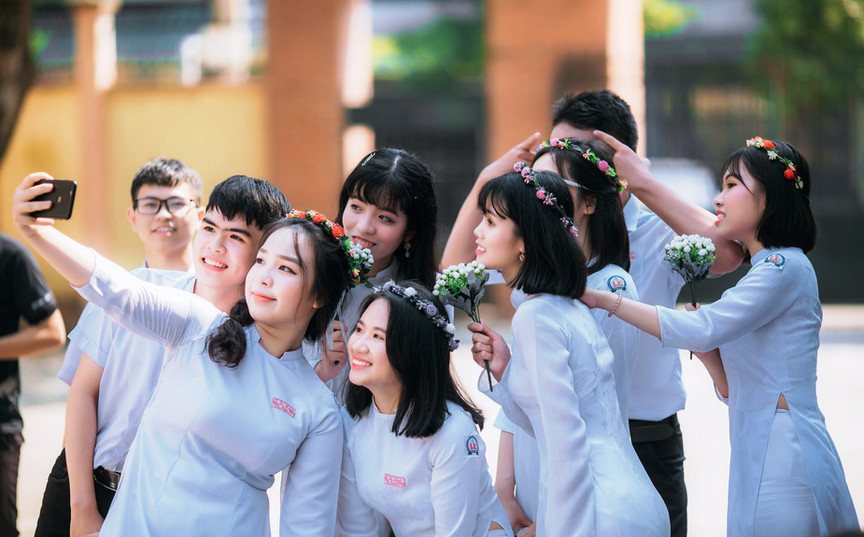 Saigon high school students taking a photo in front of their school