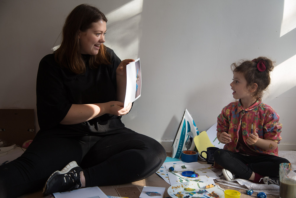 There is a person on the left wearing all black with long brown hair showing a piece of apaper wiht a work on it to a cild who is sat to the right of them , the child is between the age of 4 and 7 has various paints and pieces of paper in front of them. They are both sat on the floor with their legs crossed.