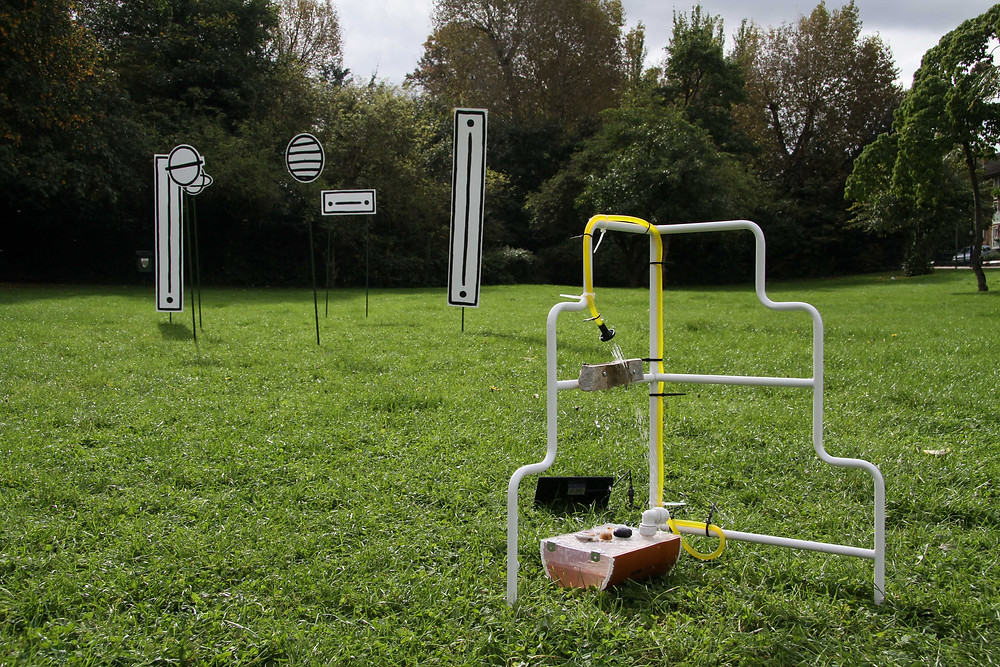 a photography of outside in a park with green grass and a wall of various types of trees in the background and grey sky. In the foreground are two works by commissioned artists, in the imdeiate froeground is a white metal frame with a staggered step shape, there is a yellow tube that is carrying water from the brown tub on the ground and showering a rock that is bolted to the metal frame, behind this is a work consisting of a cluster of black and white cut outs of circles and rectangles on poles that are stuck into the ground so that they stand up right.