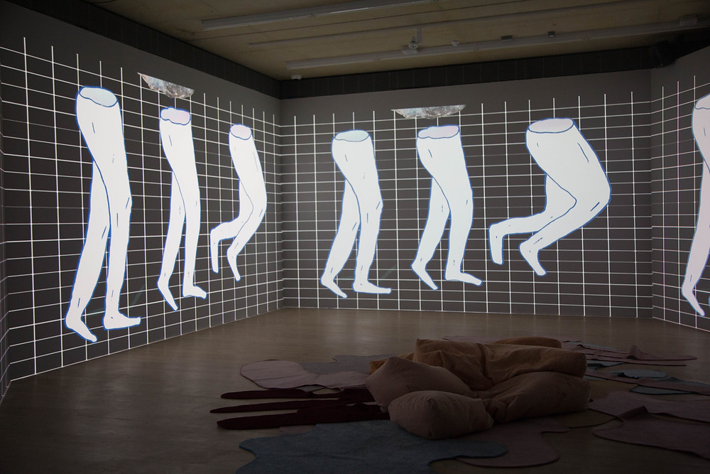 A exhibition photograph of the 4 wall projection of the show reel at Focal Point Gallery, the 4 projections show a black gacgroun with a white grid pattern with three pairs of cartoon legs in white missing the top half of the body. In the center of the projections on the floor is an artwork of blob shaped carpets and blob shaped bean bags all in pastel pinks and blues.