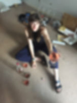 Image of Eva sat on a tiled floor with various objects around her, she is a white woman with long brown hair with a fringe, she is wearing a black vest, blue trousers and sandles, next to her is a bottle of Rosé wine and 3 glasses, she is smiling and holding another glass full of wine up to the person taking the photo
