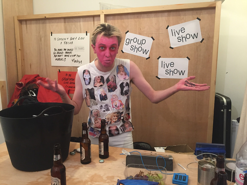 Special guest performer, Aidan Strudwick, stands behind the bar with his face painted pink.