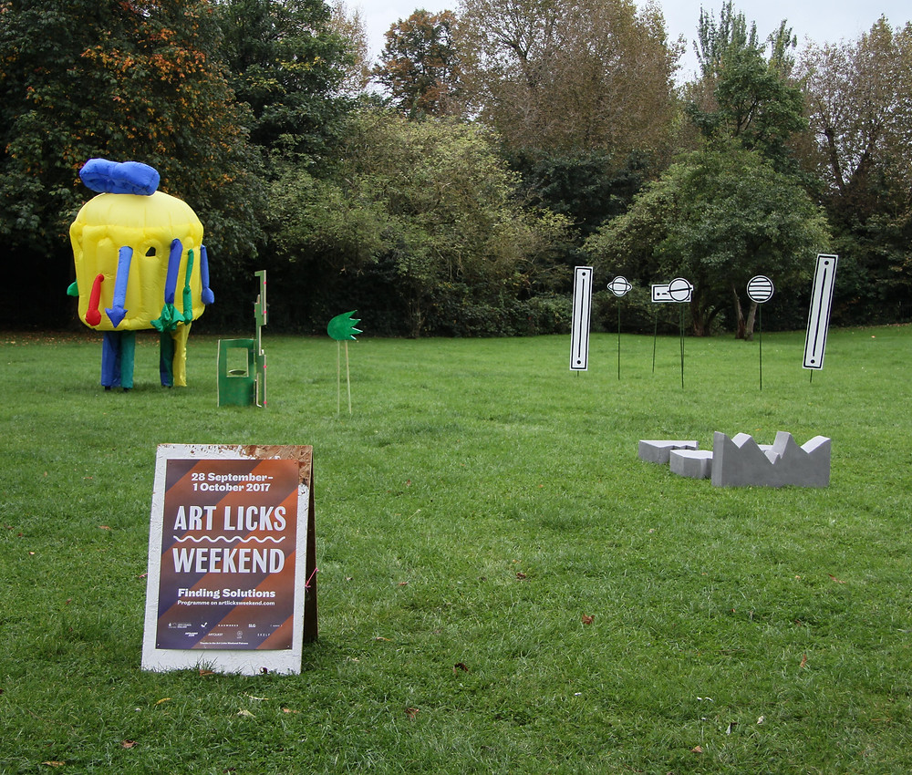 a photography of outside in a park with green grass and a wall of various types of trees in the background and grey sky. In the foreground is the Art Licks Weekend Poster on an A board, In the background are numerous works by commissioned artists, to the left is a yellow inflatable fat cylinder with various colour full strands coming off it, inside you can see two peoples legs at the bottom wearing similar primary colours, the right of it is a work of green boards cut in the block mini mall shapes and one to the side of that looks like a comet outline on two pole legs, to the far right there is a cluster of 6 monochrome shapes with white fill and black outline on green garden poles. the shapes are circular and long vertical rectangles, in front of the work is a cluster of grey blocks that are cartoon shapes of a broken block.