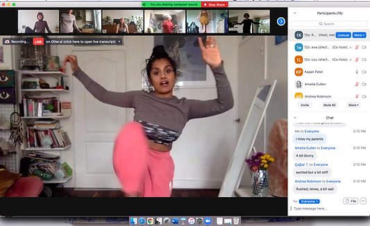 Screen shot of zoom with screens of 6 participants at the top on the frame all doing various movements i front of their cameras . Underneath is kaajel guiding everyone wearing a grey top and pink trousers. She is holding up her leg and has her arms in the air. behind her is a white wall and door and bookshelves.