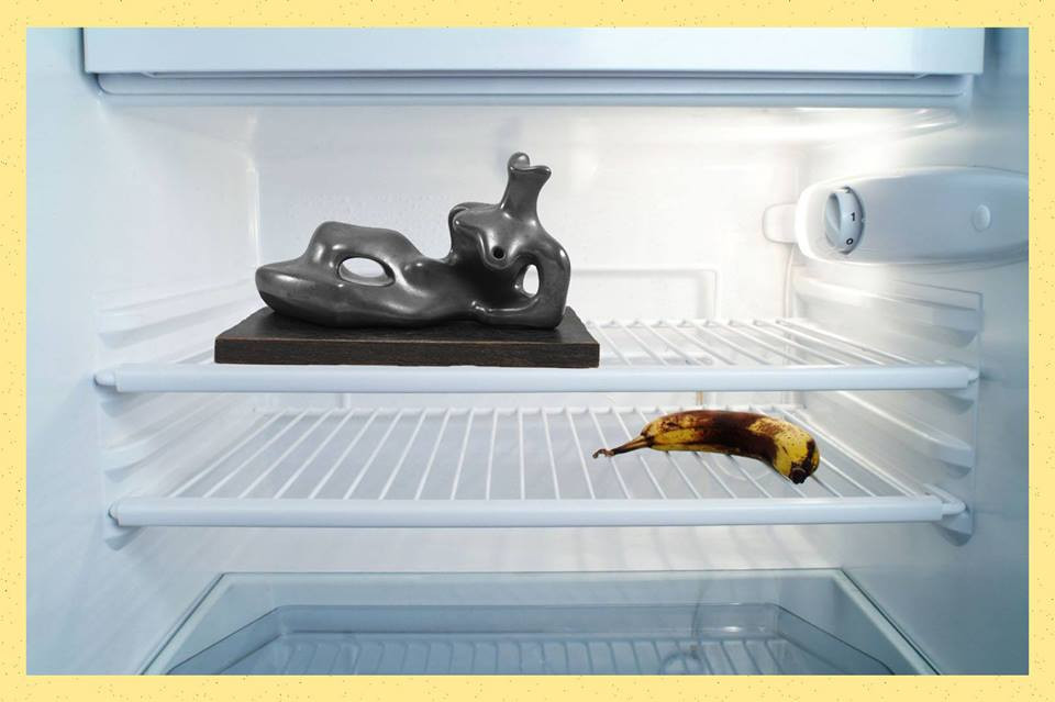 A yellow framed photograph of the inside of a fridge with two slotted shelves. On the top shelf, slightly to the left is a black marble abstract modernist figure in the style of artists like henry moore or barbara hepworth. on the shelf below is bruised banana.