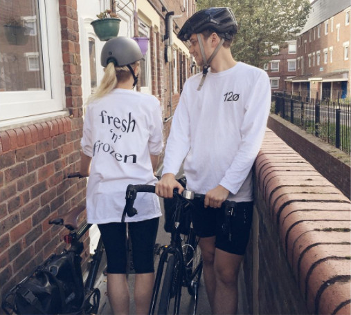 two members of 12o stood outside a residential building Lou has her back to the camera and is showing the back of her white top with the logo fresh and frozen printed large on it, jacob is looking at lou but showing the front of his top . they are both wearing cycle helmets and holding their bikes.