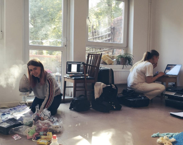 two artists at work in the studio, the left person has various bundles of fabric a threads in front of them and an iron in their right hand, they are holding it up to the camera so that is steams. the person to right is coruched working on a laptop, the room is white walled with a window and glass door showing an outside space.