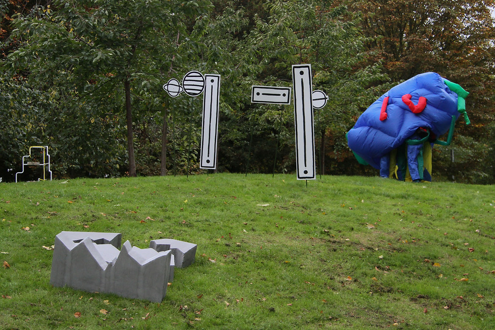 a photography of outside in a park with green grass and a wall of various types of trees in the background. In the foreground are numerous works by commissioned artists, to the right is a blue inflatable with various colour full strands coming off it, inside you can see two peoples legs at the bottom wearing similar primary colours, to the left there is a cluster of 6 monochorme shapes in white with black outline on green garden poles stuck into the ground so to make them stand upright. the shapes are circular and long vertical rectangles, to the far left the is a white frame in the shape of steps. In the immediate front is a cluster of grey blocks that are cartoon shapes of a broken block.