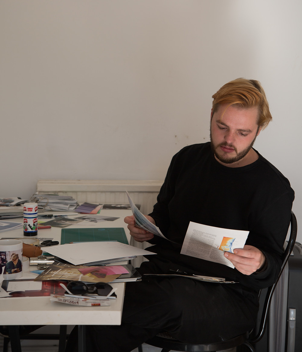 an artist sat at a desk with various pieces of papers an photographed in front of them and tools, they are wearing all black and have short blond hair , they are looking down at two pieces of paper that they are holding in each hand.