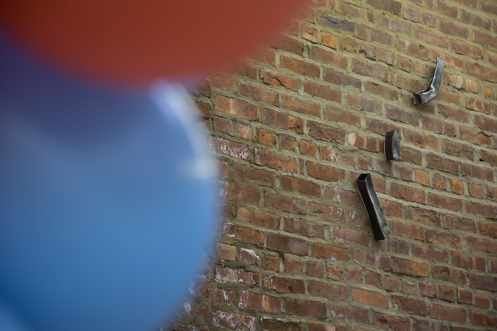 foreground are out of focus red a blue balloons and in the background shows the brick wall with three ceramic pieces in black metalic colour placed diagonally and staggered, the shapes are square cylinders.