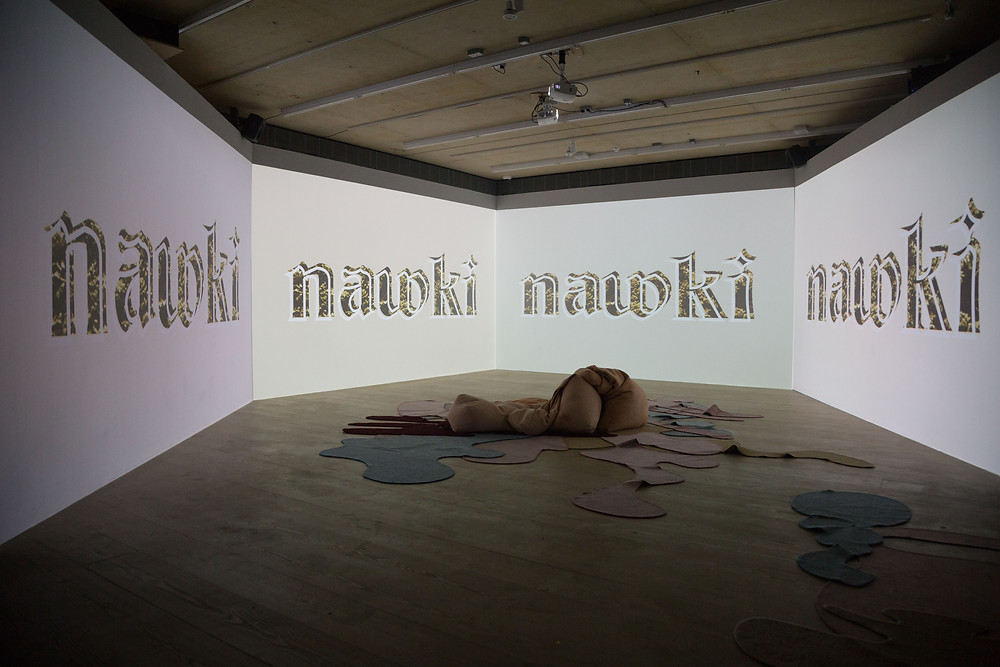 A exhibition photograph of the 4 wall projection of the show reel at Focal Point Gallery, the 4 projections are of the nawki logo. in the center of the projections on the floor is an artwork of blob shaped carpets and blob shaped been bags all in pastel pinks and blues.